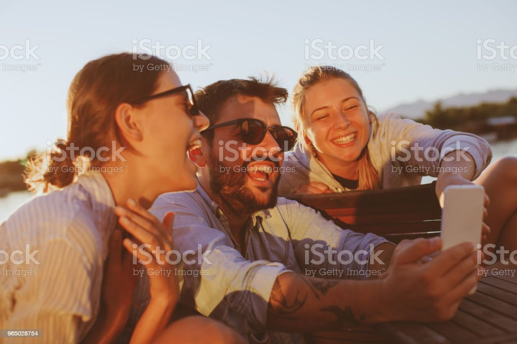 Two young woman and man using smartphone by the river and smiling royalty-free stock photo