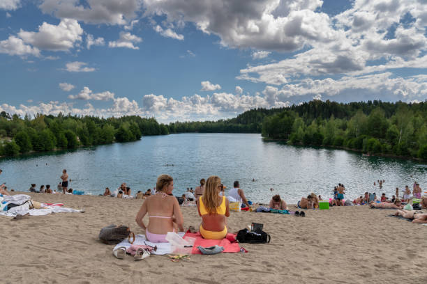 Zwei junge Frau und viele Leute Sonnen und mit Picknick an einem Strand am See. – Foto