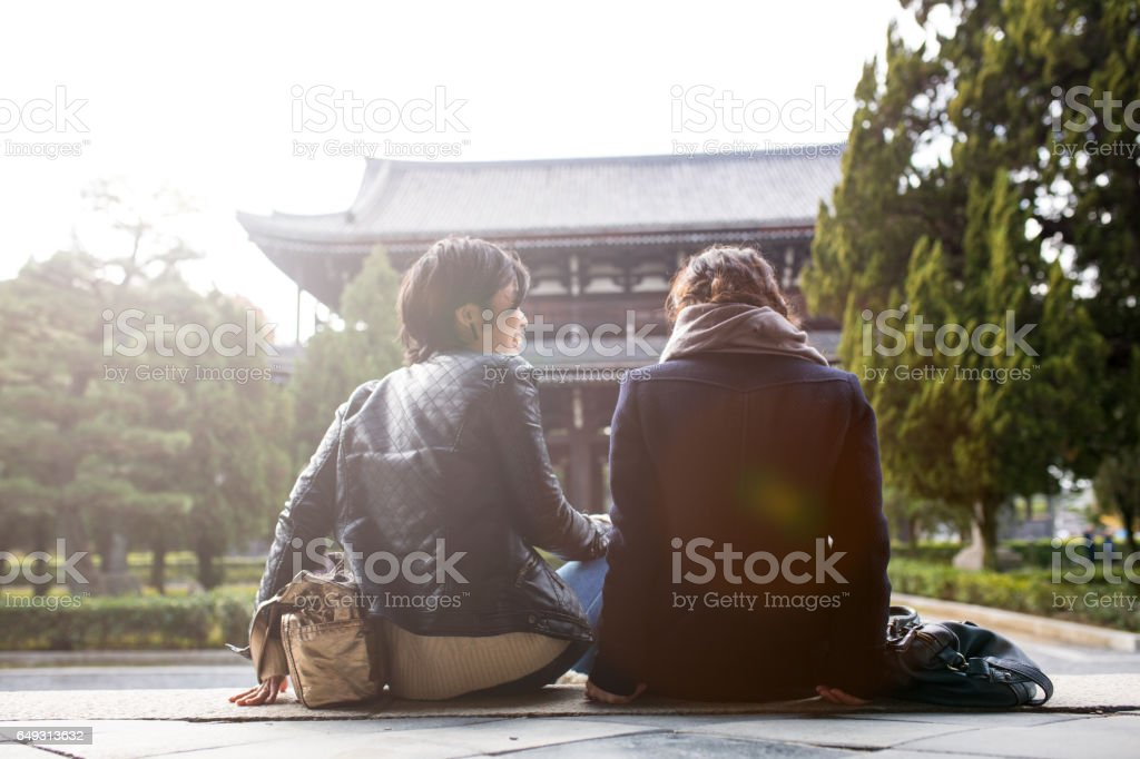 Two young woman chatting at a temple in Kyoto, Japan stock photo