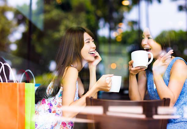 zwei junge frau plaudern in einem coffee shop - teeladen stock-fotos und bilder