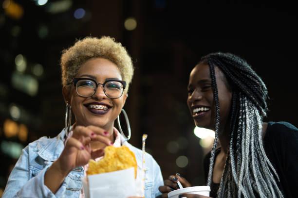 dois jovem comendo pastel na rua depois do trabalho - pastel de feira - fotografias e filmes do acervo