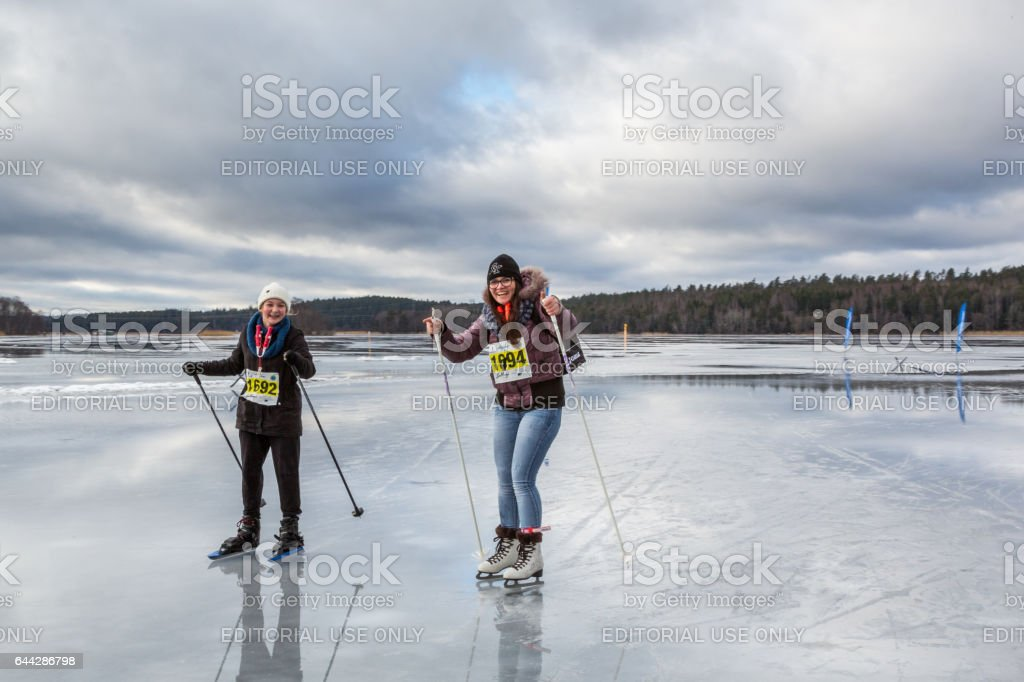 Two young woman ice skating together on wet ice. royalty-free stock photo