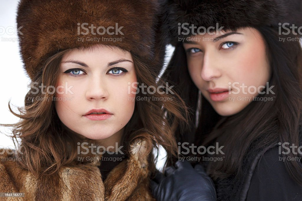 Two young woman in fur hats at winter forest royalty-free stock photo
