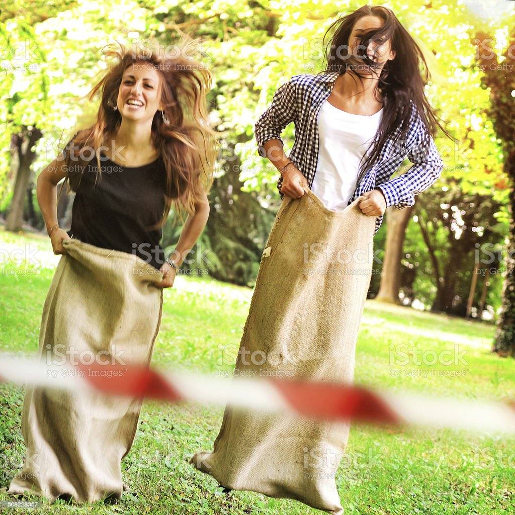 Two Young Woman Playing at Sack Race stock photo