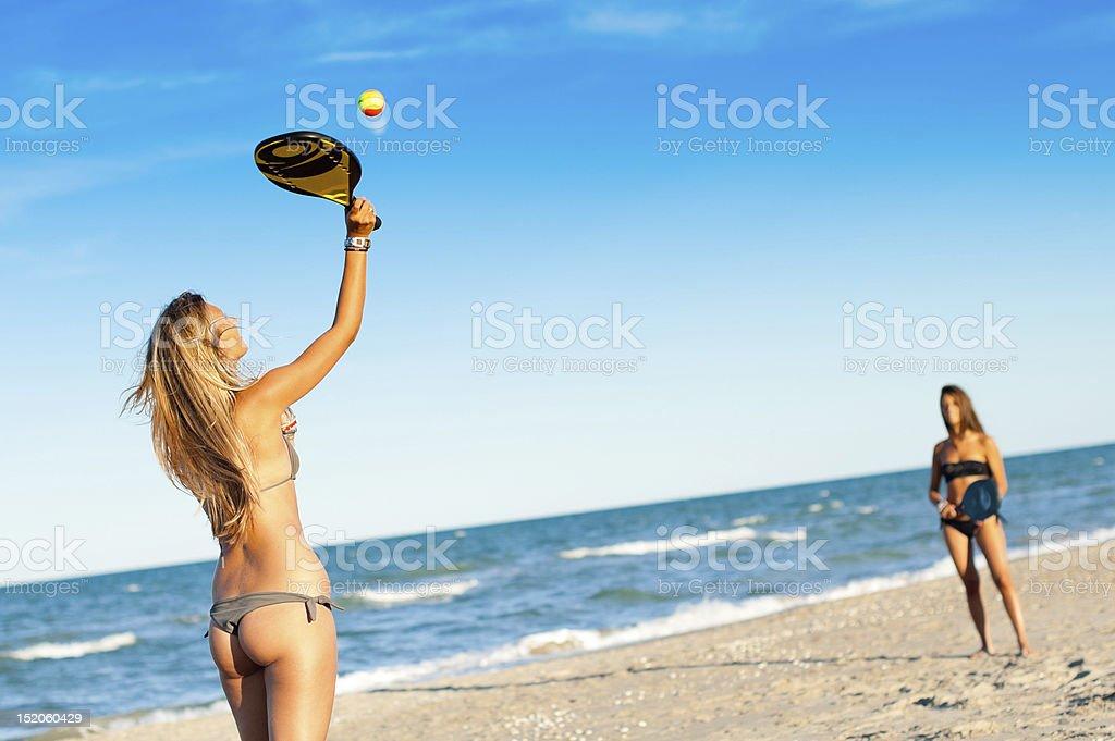 Due giovane donna giocando a tennis sulla spiaggia - foto stock