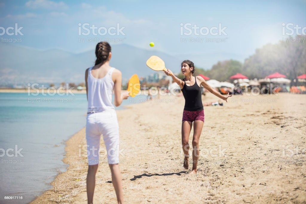 Two young woman playing beach tennis royalty-free stock photo