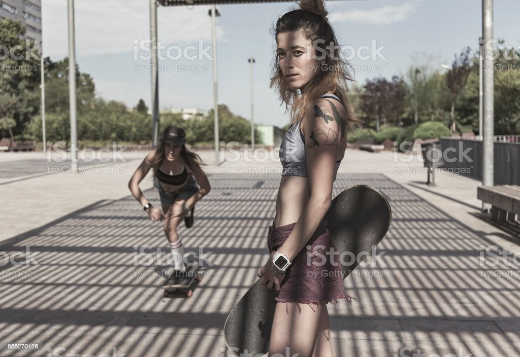 Two young woman riding skateboards stock photo
