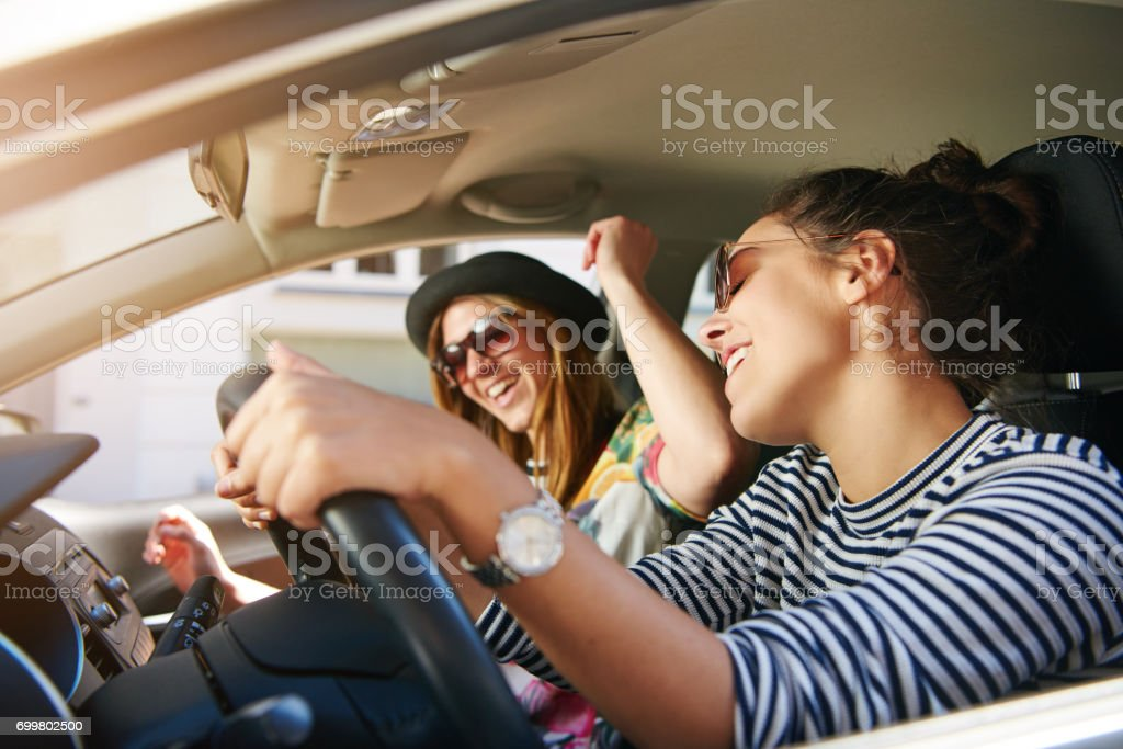 Two young woman singing along in the car stock photo