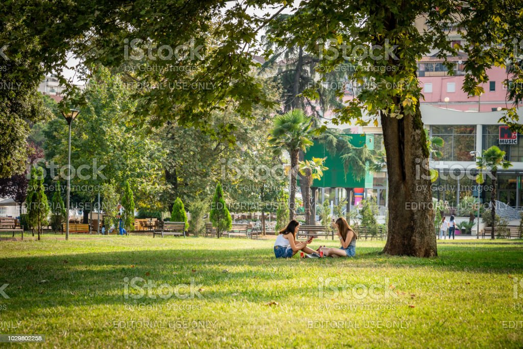 Two young woman sitting resting under a large tree in a city park in Tirana Albania. stock photo