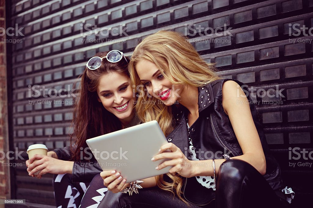 Two young woman using digital tablet on the street Two young women sitting on the city street, drinking take away coffe and using digital tablet together. Black background. 20-24 Years Stock Photo