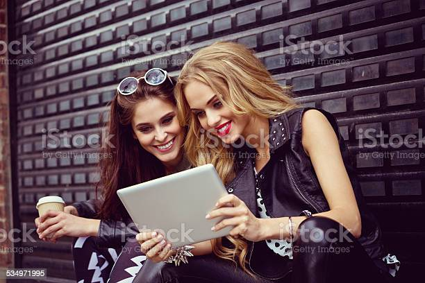 Two Young Woman Using Digital Tablet On The Street Stock Photo - Download Image Now