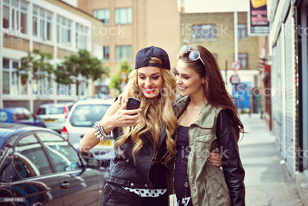Two young woman using smart phone on the street Two happy friends standing on the street and using smart phone.  20-24 Years Stock Photo