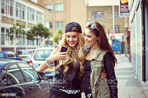 Two Young Woman Using Smart Phone On The Street Stock Photo - Download Image Now