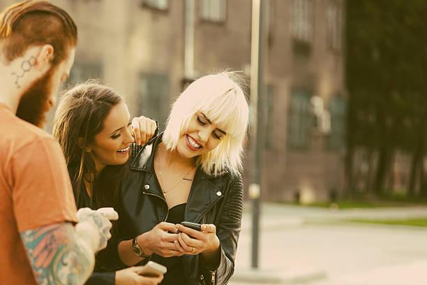 zwei junge frau mit smartphones im freien - freundin tattoos stock-fotos und bilder