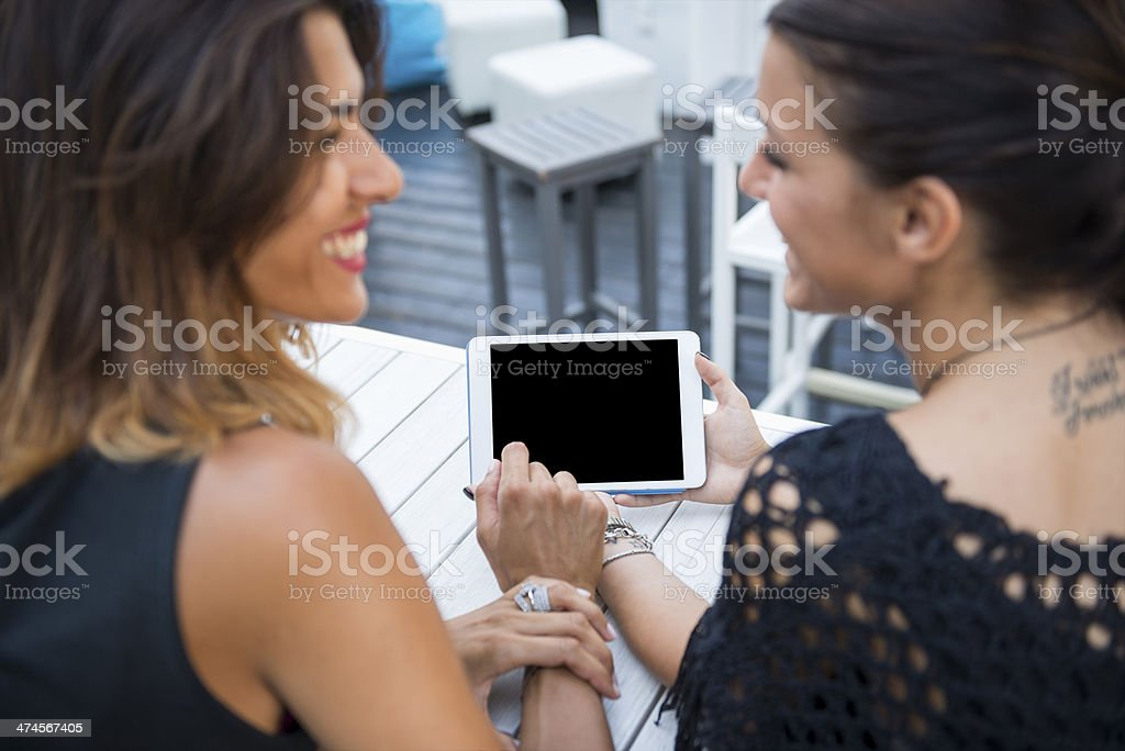 Two young woman with digital tablet at the cafè stock photo