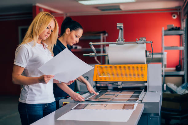 Two young woman working in printing factory stock photo
