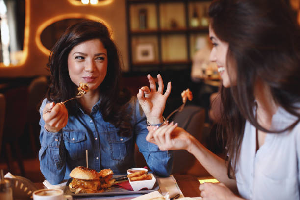 Two young women at a lunch in a restaurant stock photo