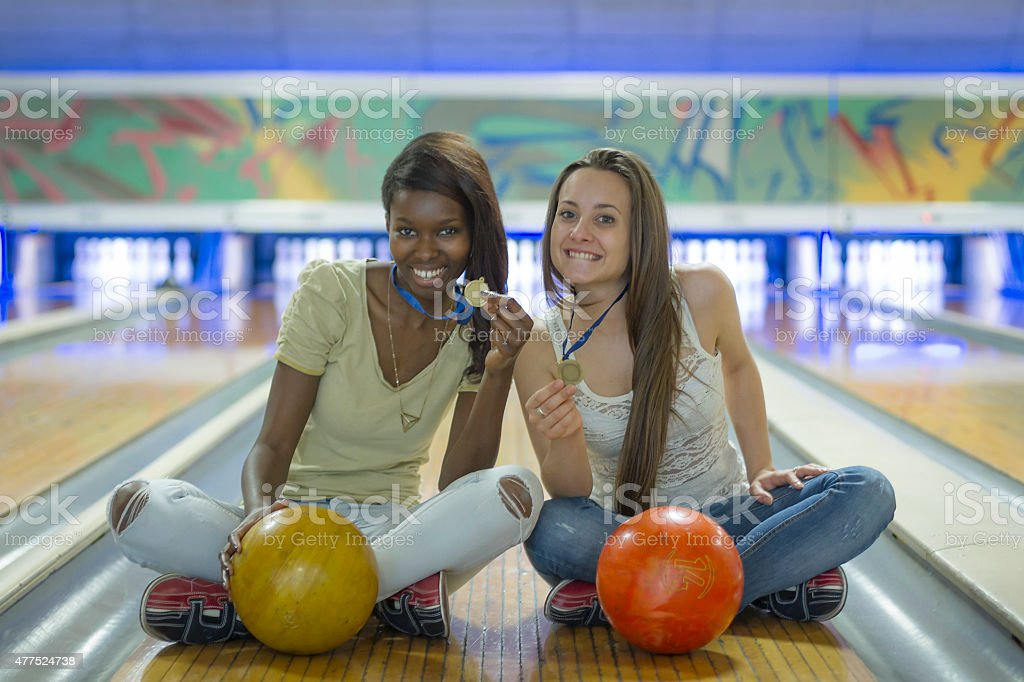 Two young women at bowling holding medals stock photo