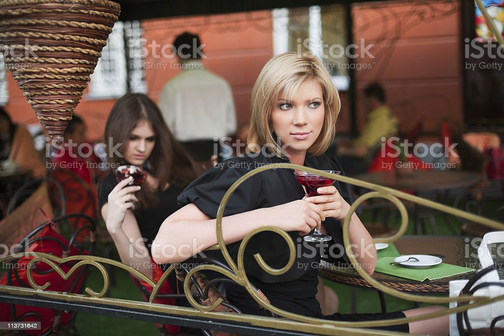 Two young women at sidewalk cafe royalty-free stock photo