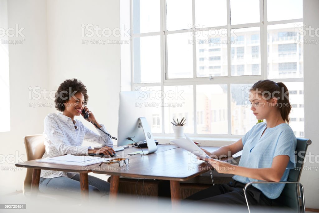 Two young women at work, on the phone and reading documents stock photo