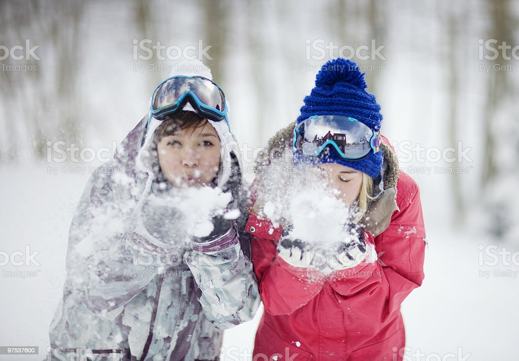 Two young women blowing snow at the camera. royalty-free stock photo
