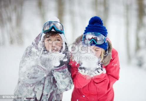 Two Young Women Blowing Snow At The Camera Stock Photo & More Pictures of 20-24 Years