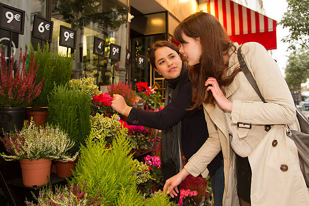 Two young women buying flowers stock photo