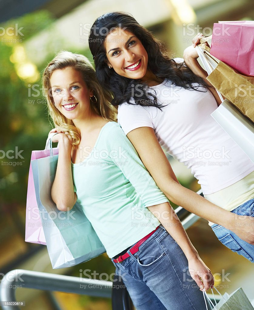 Two young women carrying their shopping bags and smiling royalty-free stock photo