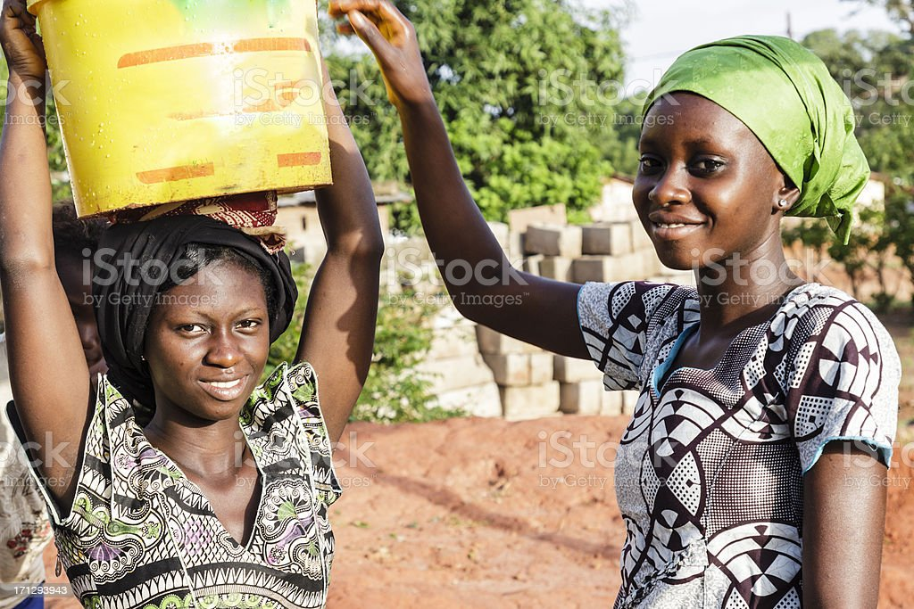 Two young women carrying water in Africa stock photo