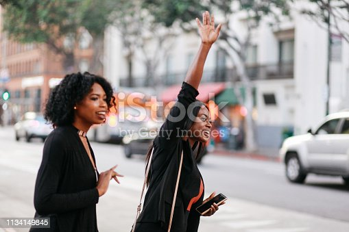 istock Two young women catching a cab on the streets of downtown Los Angeles 1134149845
