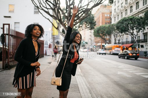 istock Two young women catching a cab on the streets of downtown Los Angeles 1134362627