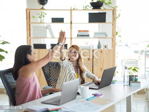 1031394114istockphoto Two young women celebrating with high five at the office 1094523176