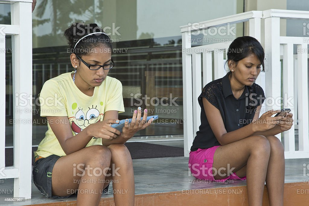Two Young Women  checking text messages on IPad and IPhone royalty-free stock photo