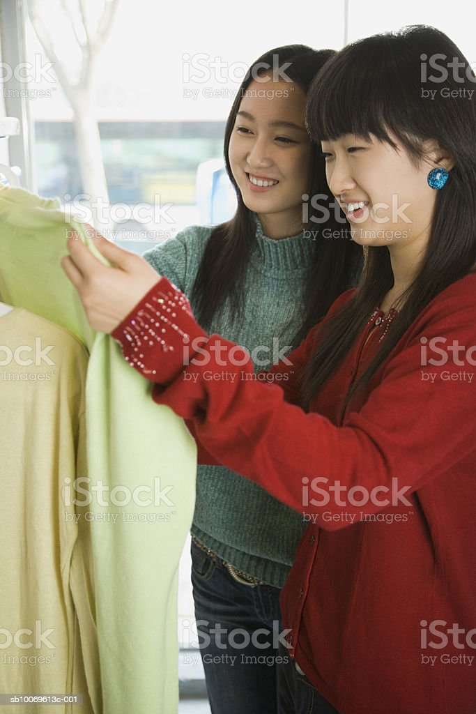 Two young women choosing dresses in shop, smiling royalty-free stock photo