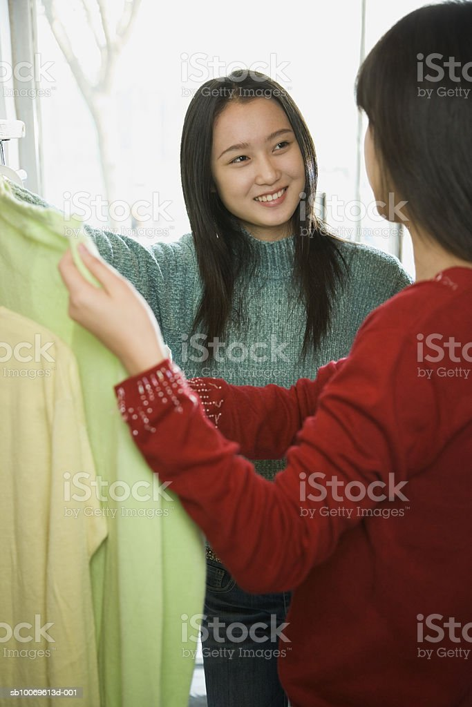Two young women choosing dresses in shop, smiling photo libre de droits