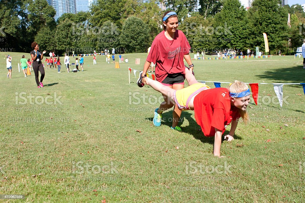 Two Young Women Compete In Wheelbarrow Race At Summer Fundraiser stock photo