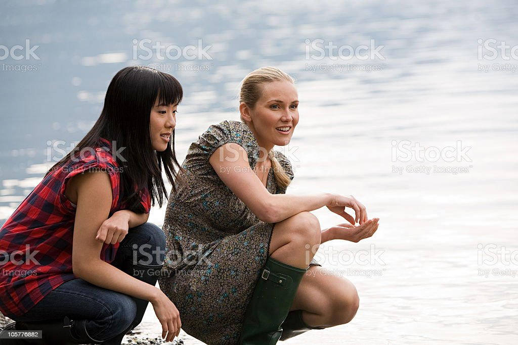 Two young women crouching near lake royalty-free stock photo