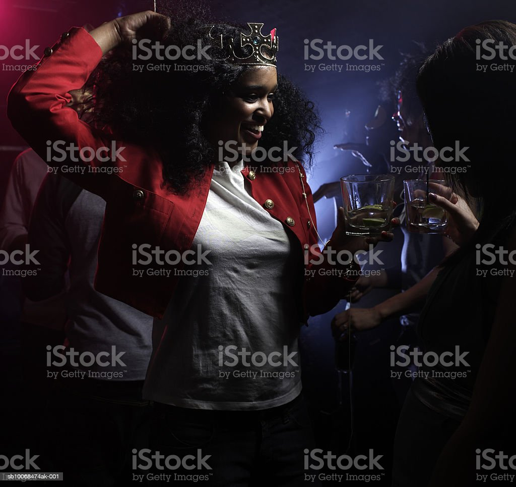Two young women dancing in night club, one wearing crown royalty-free stock photo