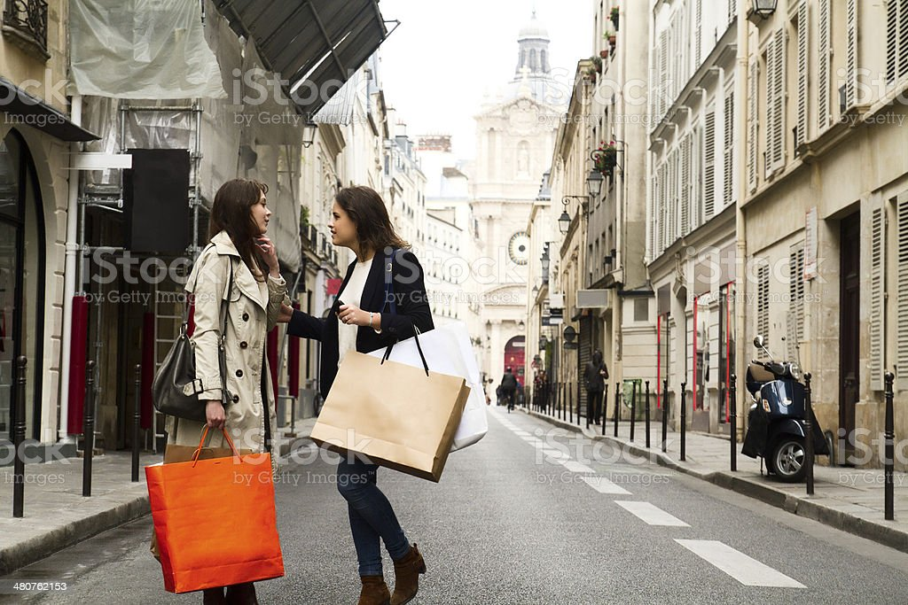 Two young women discussing in the middle of the street Two young women discussing in the middle of the street during a session of shopping Adult Stock Photo