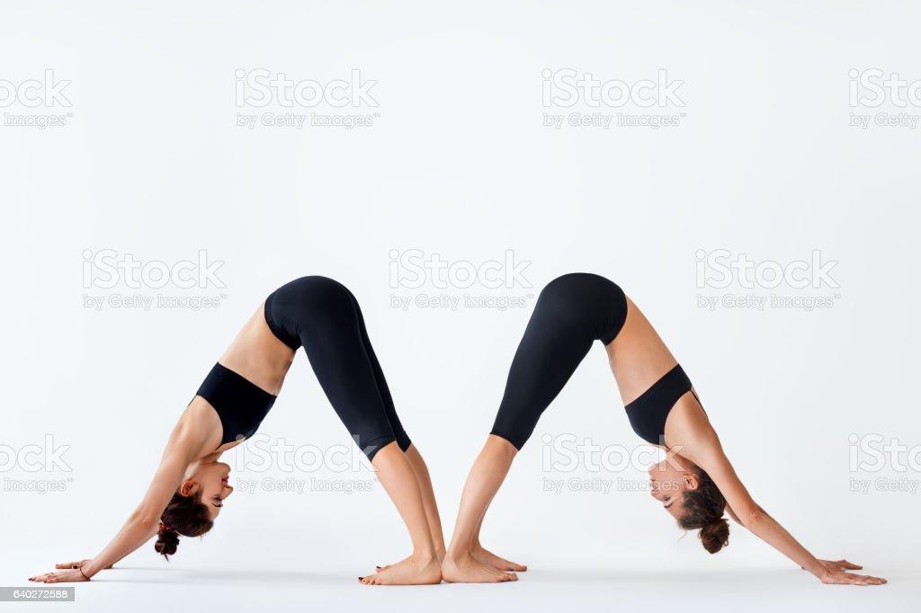 Zwei junge Frauen beim yoga-asana nach unten schauenden Hund