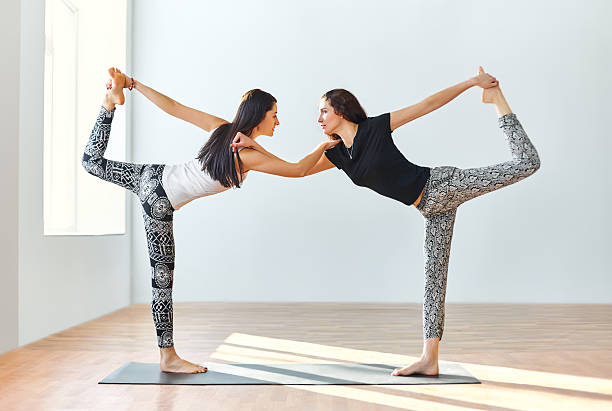 Two Young Women Doing Yoga Asana Lord Of Dance Pose Stock Photo