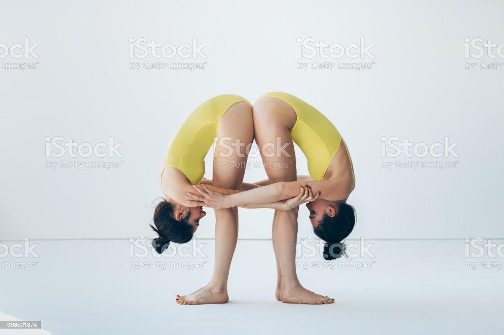 Two young women doing yoga asana standing forward bend pose stock photo