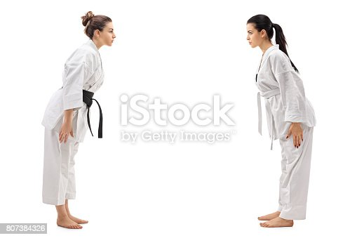 istock Two young women dressed in kimonos bowing to each other 807384326