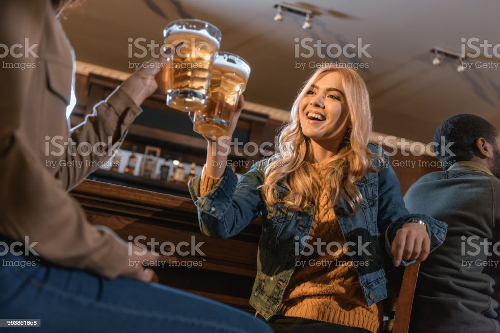 two young women drinking beer at bar - Royalty-free Adult Stock Photo