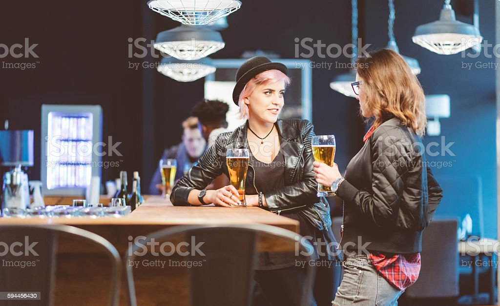 Two young women drinking beer in a pub Two cool young women drinking beer in th pub, talking together. Adult Stock Photo