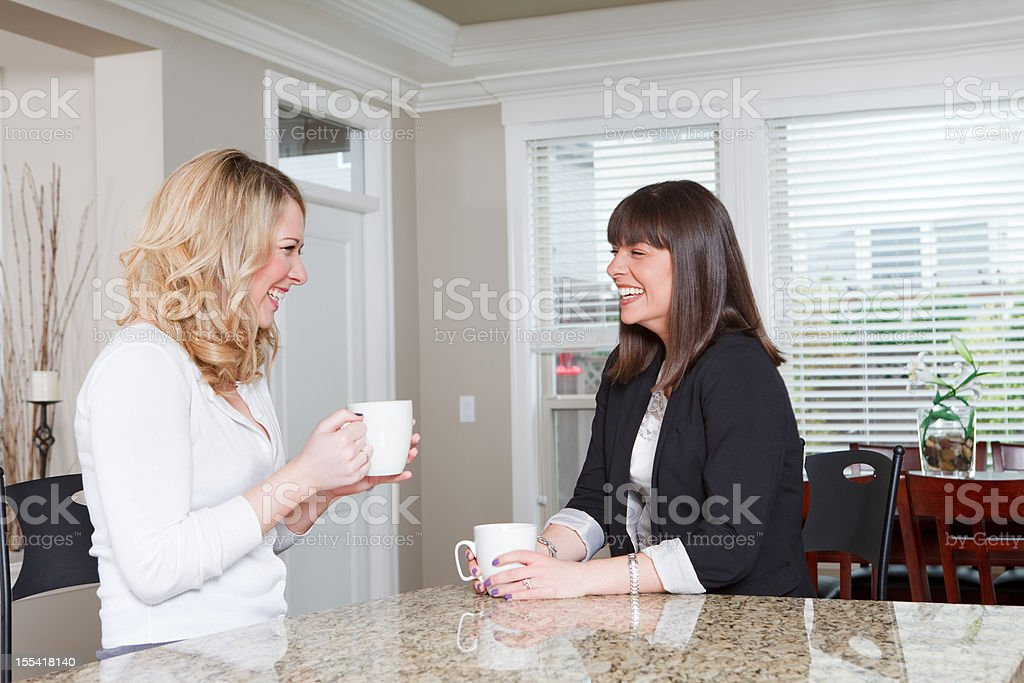 Two young women drinking coffee and laughing royalty-free stock photo