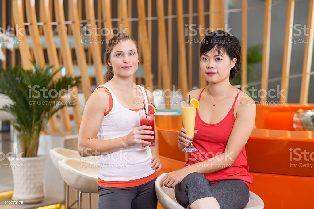 Two Young Women Drinking Smoothies in Sport Bar stock photo