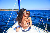 Two young women embracing and having fun on yacht