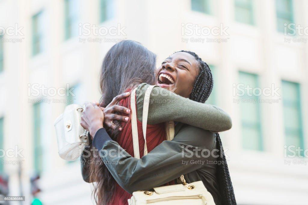 Zwei junge Frauen an Straßenecke umarmen – Foto
