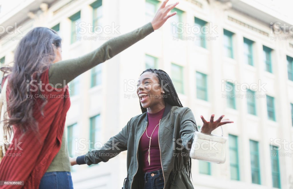 Two young women embracing on street corner stock photo